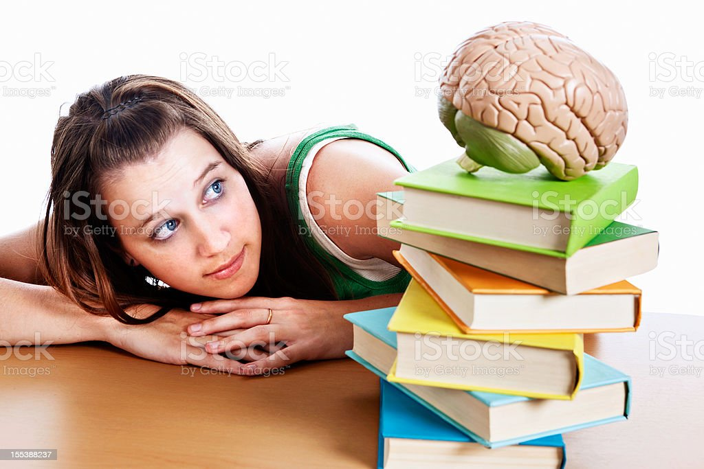 Cute young woman looks at books and model brain royalty-free stock photo