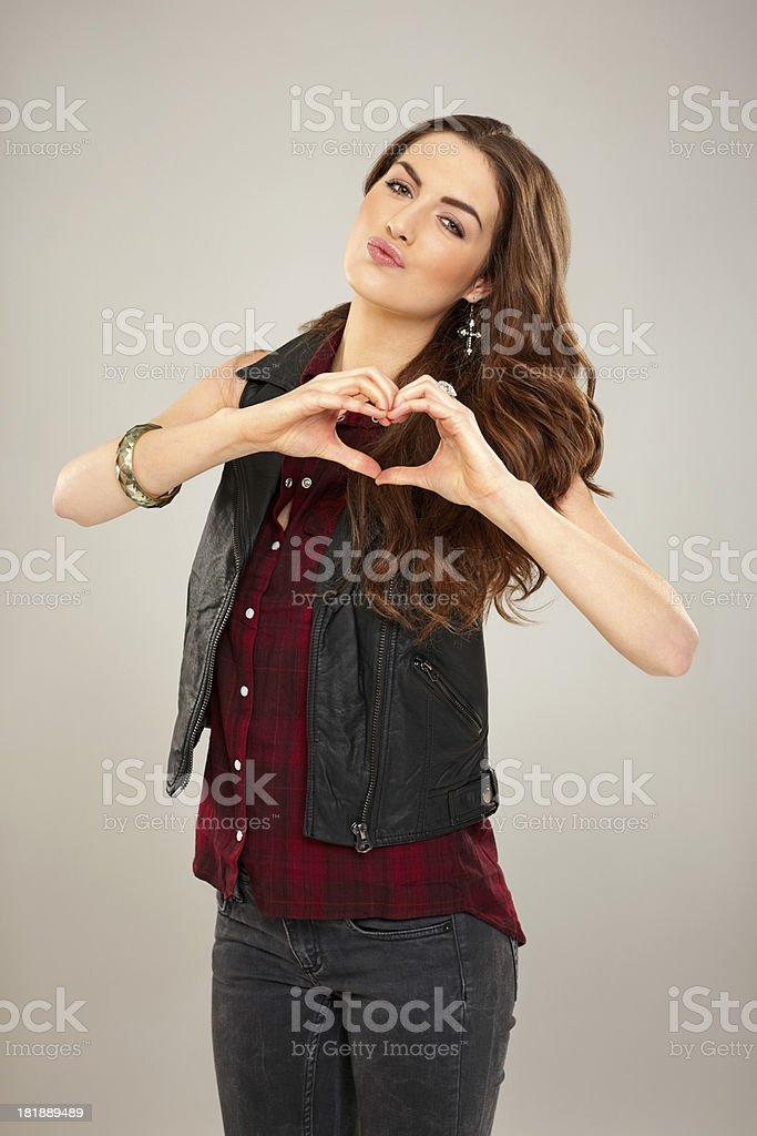 Cute young woman making heart shape with her hand royalty-free stock photo