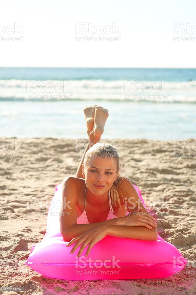 Cute young woman on a pink water float at the sea shore stock photo