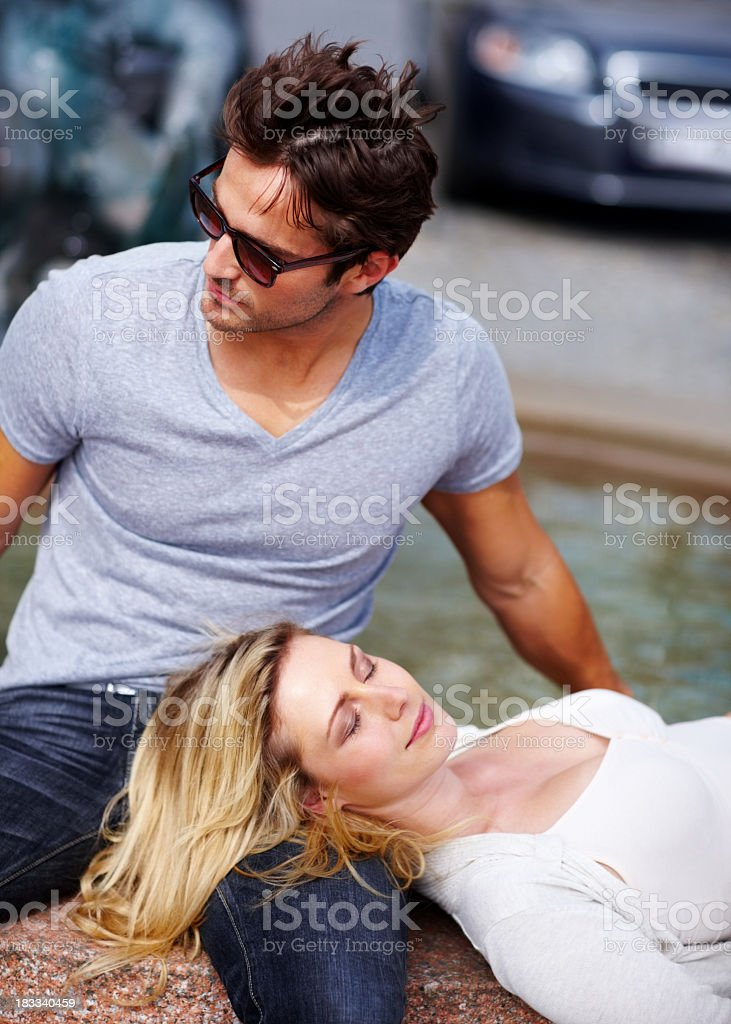 Cute young woman relaxing in her boyfriends lap royalty-free stock photo