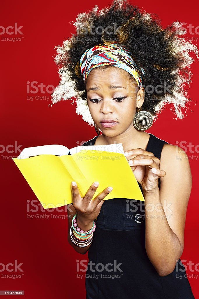 Cute young woman seems bothered by  book she holds royalty-free stock photo