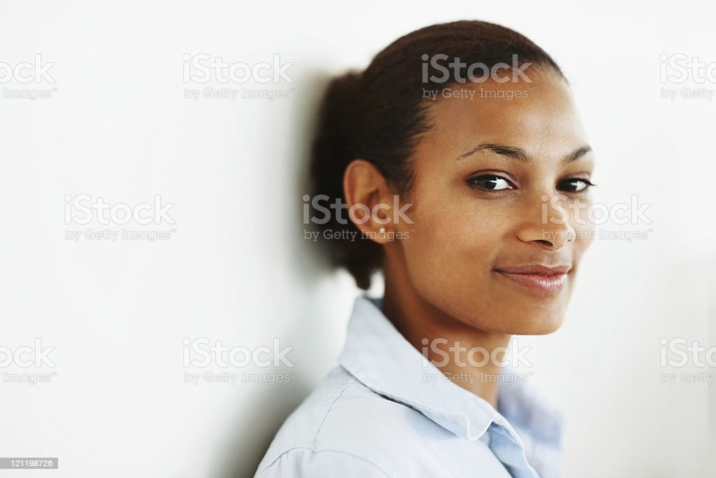 Cute young woman smiling against a white wall stock photo