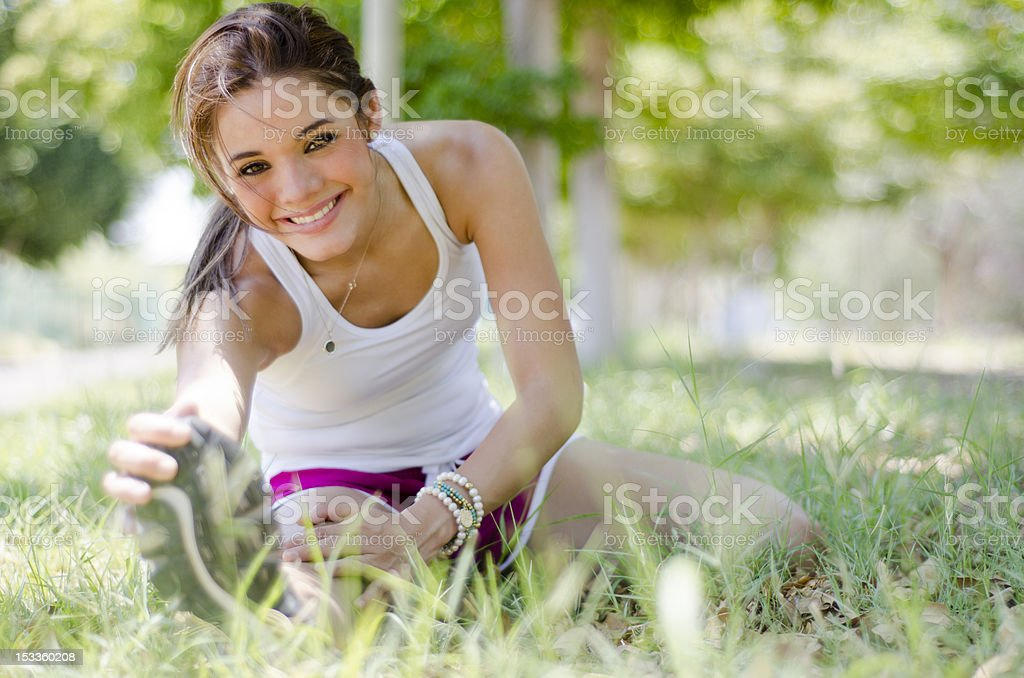 Cute young woman stretching at a park stock photo