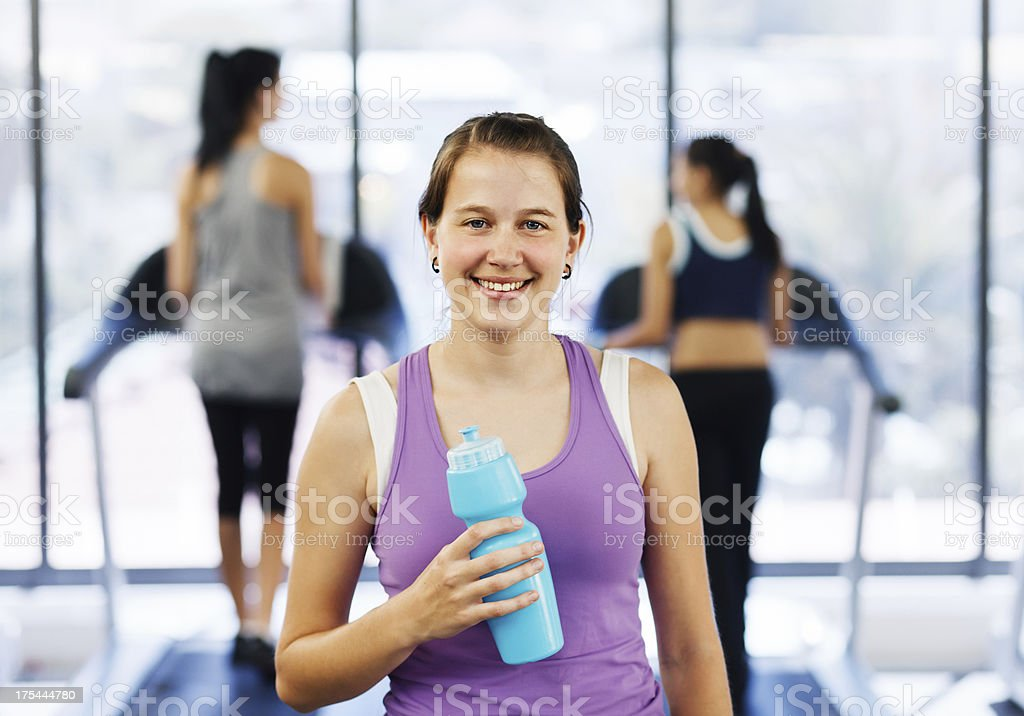 Cute young woman takes a water break at gym stock photo