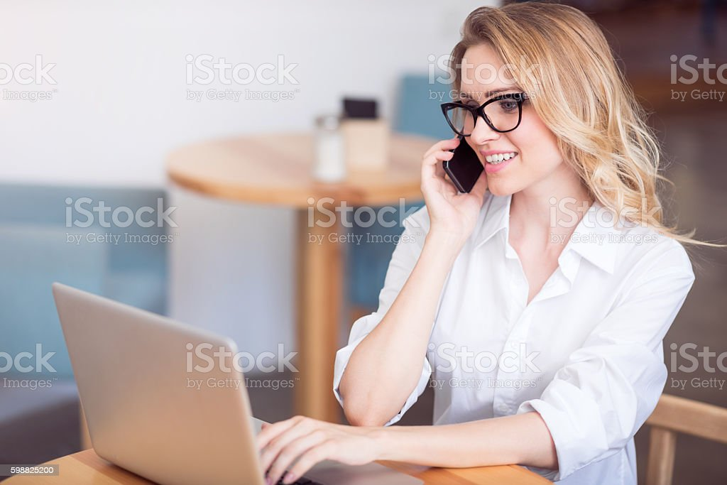Cute young woman using laptop and phone stock photo