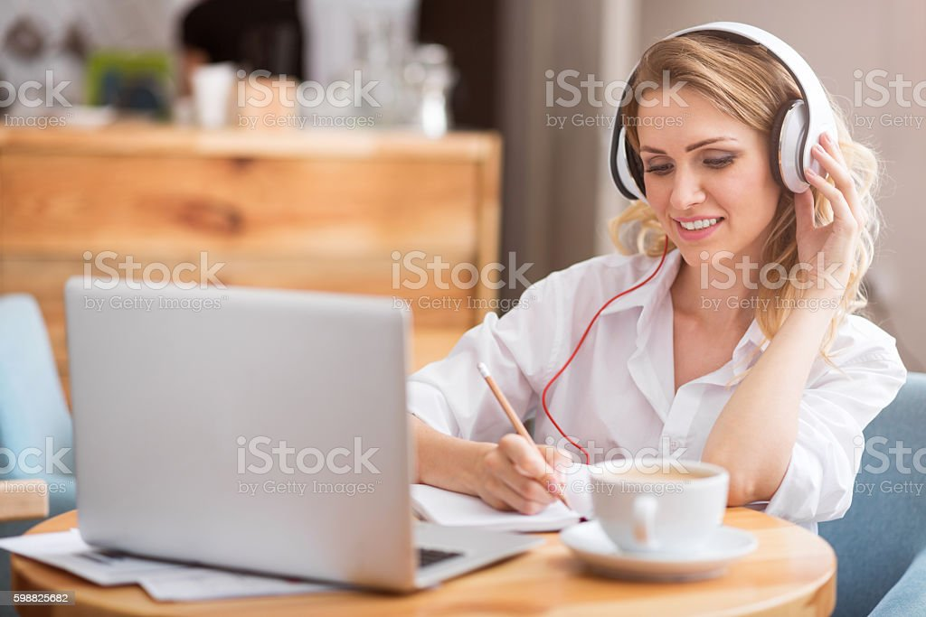 Cute young woman writing something down stock photo