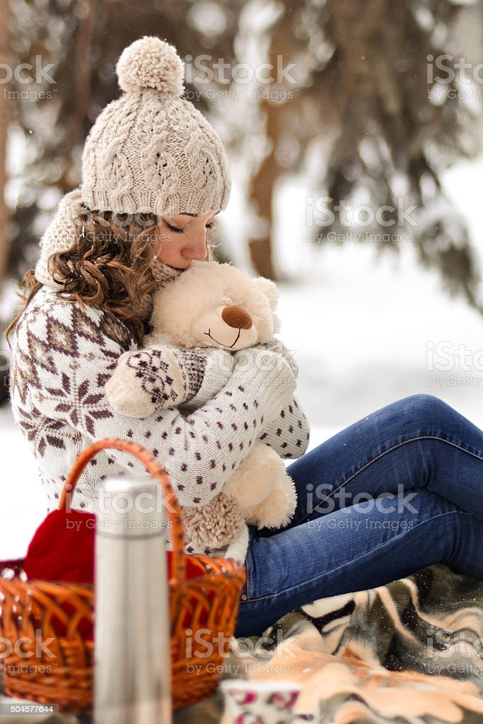 Cute,pretty girl with warm sweater hug little,fluffy toy stock photo