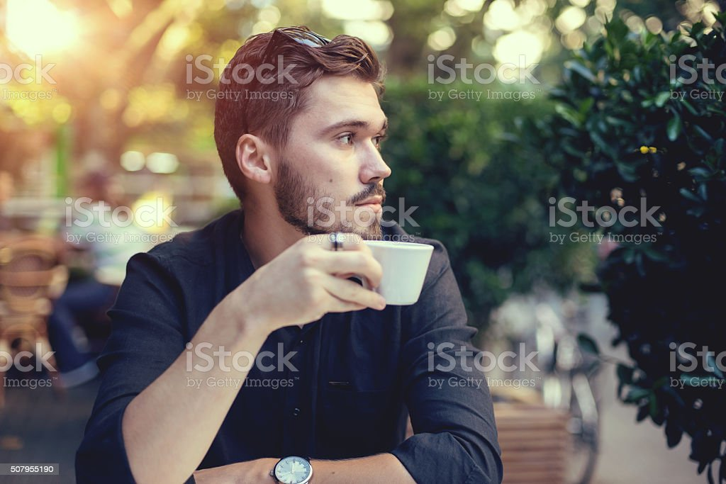 Cutie man with cup of coffee looking at mobile phone stock photo