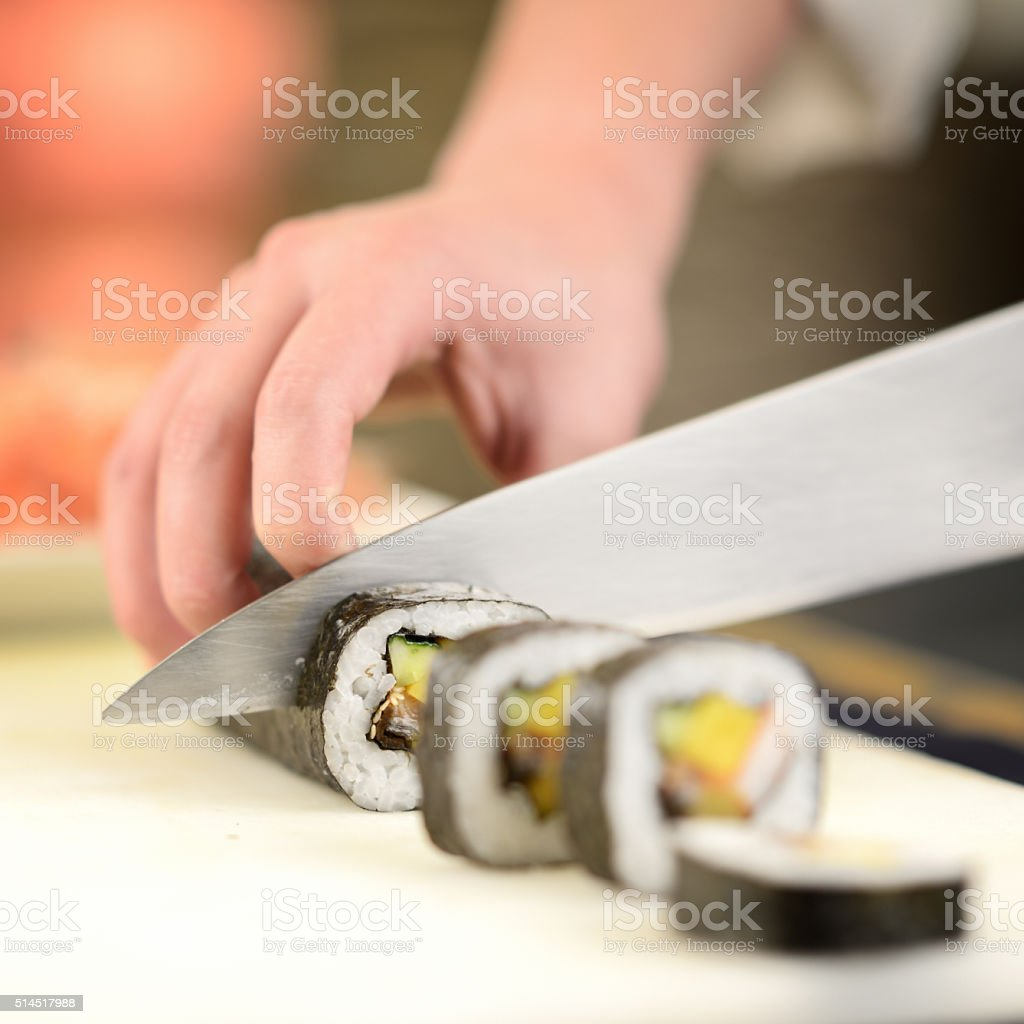 Cuting the sushi roll stock photo
