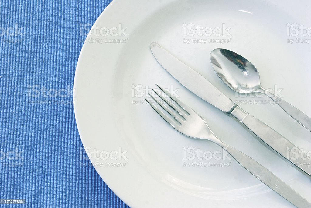 Cutlery and Plate on Blue royalty-free stock photo