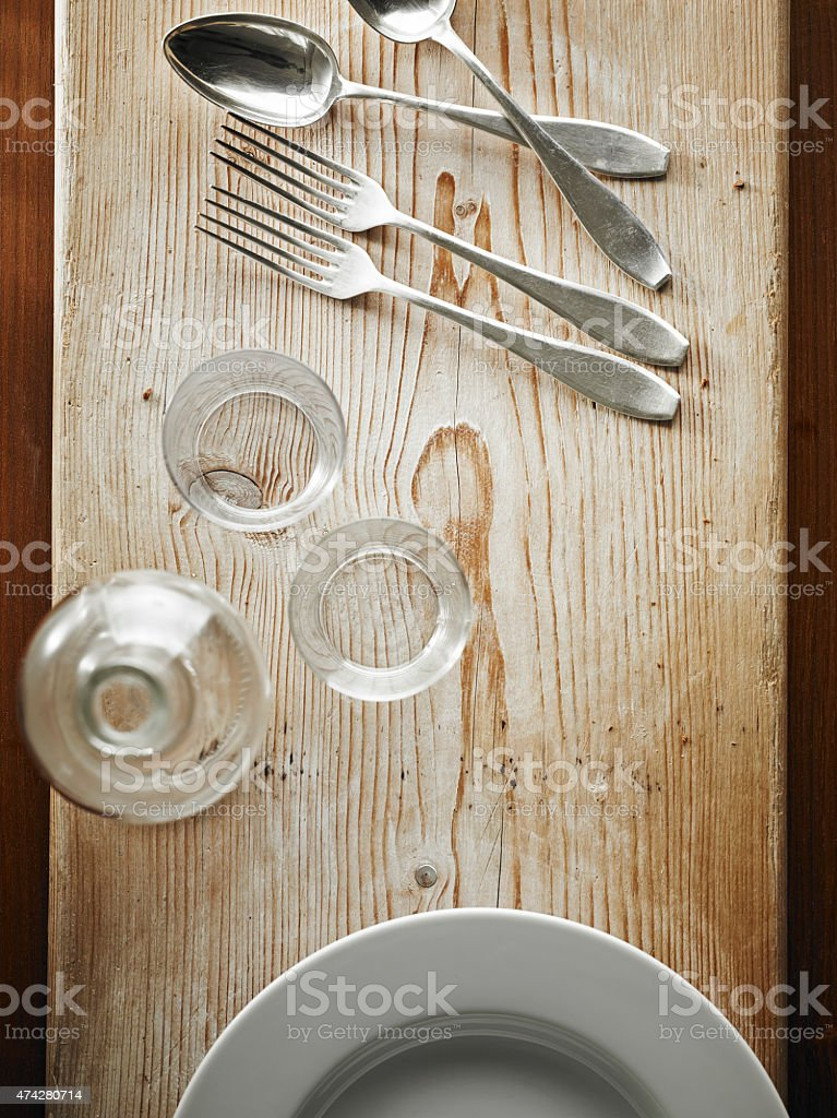 Cutlery and tableware on wooden board stock photo