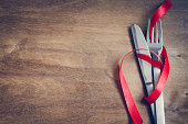 Cutlery Decorated with Red Ribbon on Wooden Background.