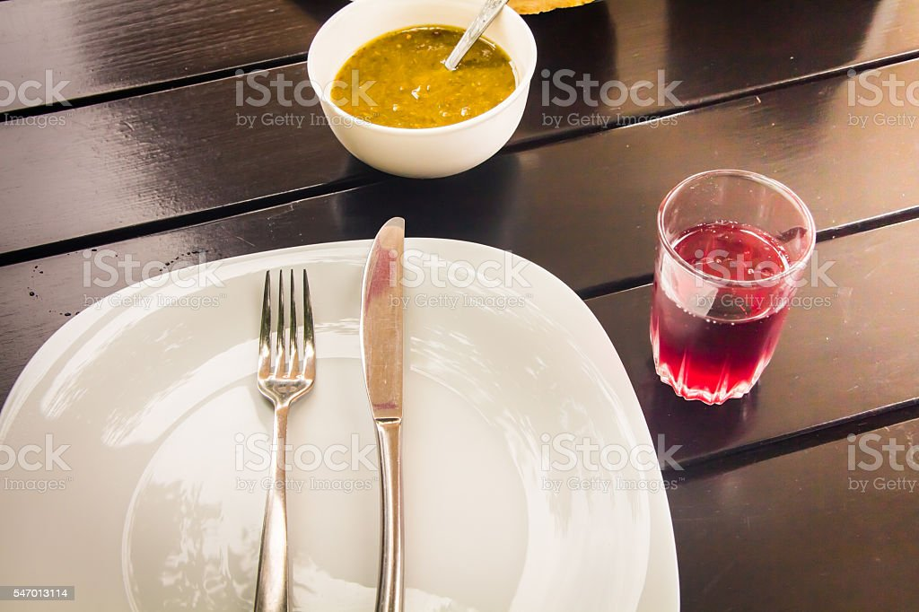 Cutlery fork and knife on a white plate stock photo