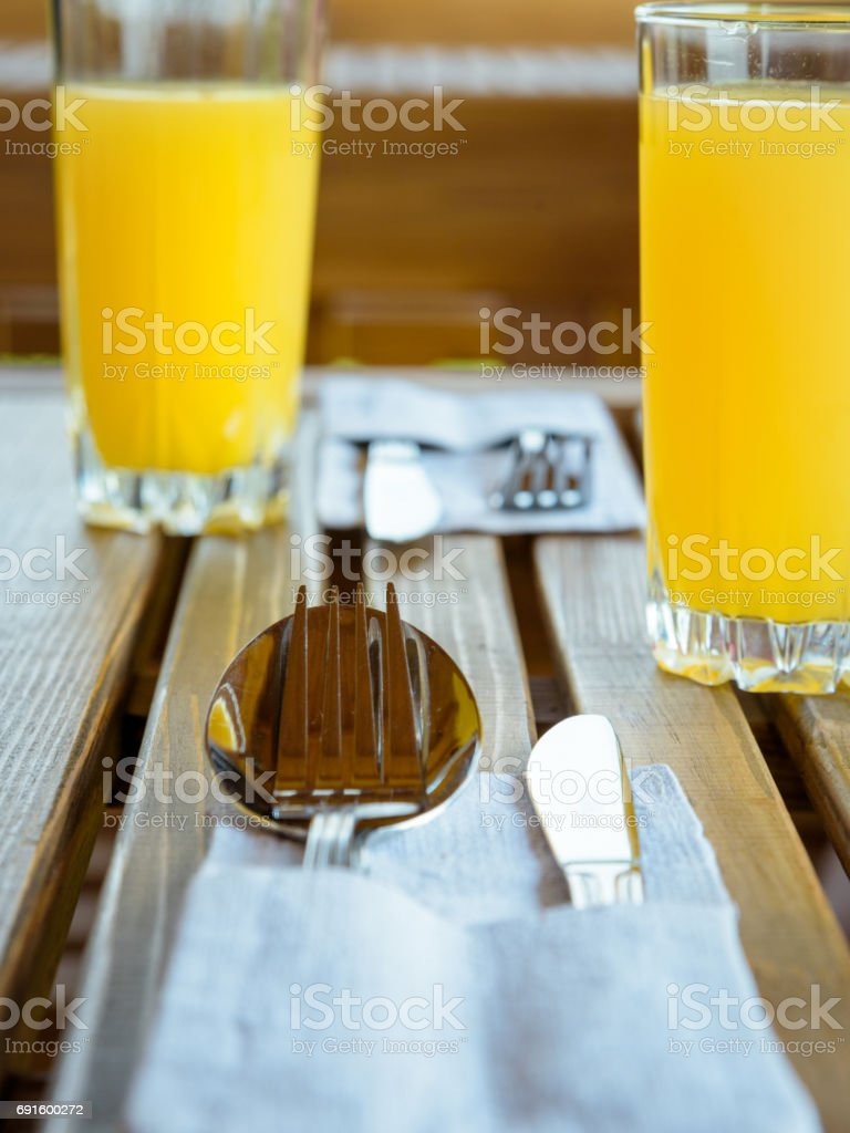 Cutlery in linen napkin, juice on wooden table, set for two stock photo