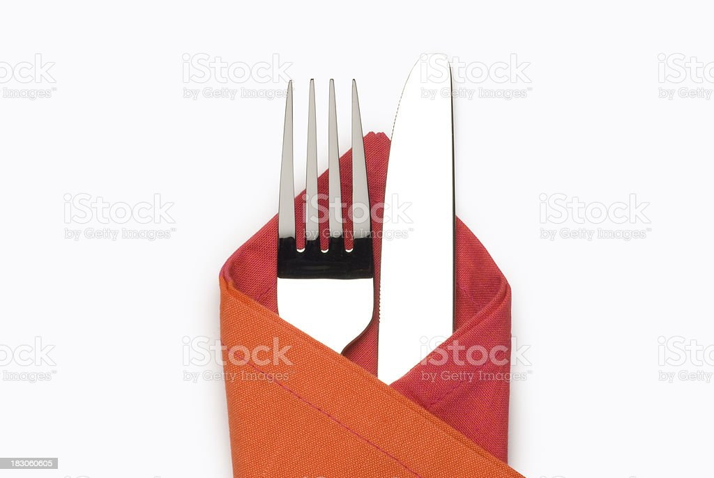 Cutlery in orange napkin isolated with clipping path stock photo