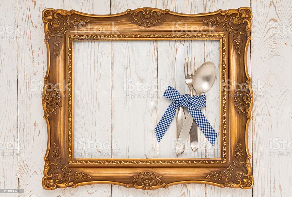 Cutlery in picture frame on wooden table stock photo