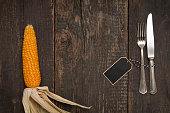 Cutlery on rustic old wooden table with corn