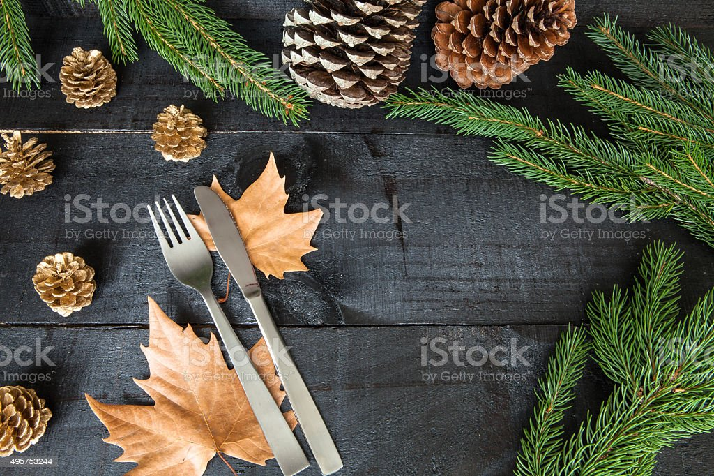Cutlery, pine cones and branches on wooden background stock photo