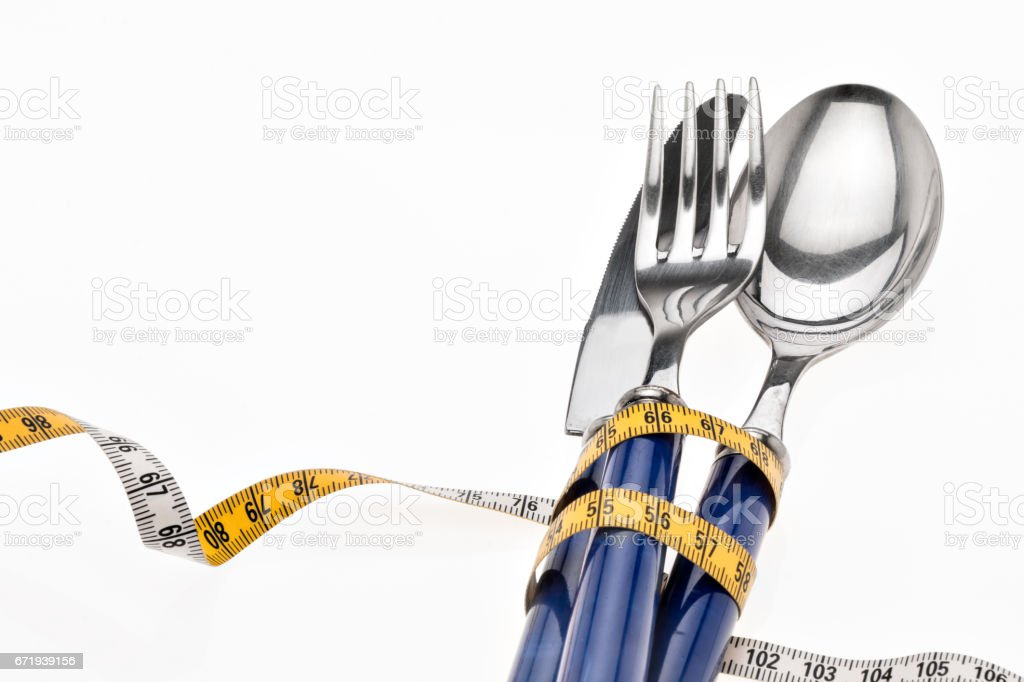 Cutlery wrapped with a tape measure, symbol for a diet stock photo