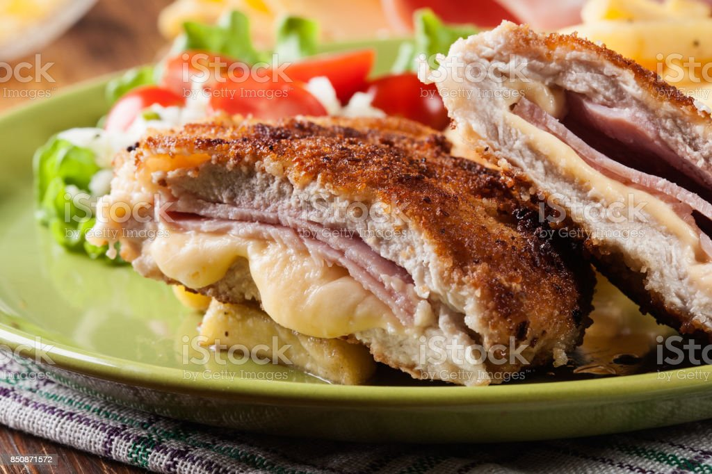 Cutlet Cordon Bleu with pork loin served with French fries and salad stock photo