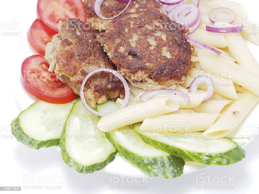 Cutlets with vegetables and pasta on a white background stock photo