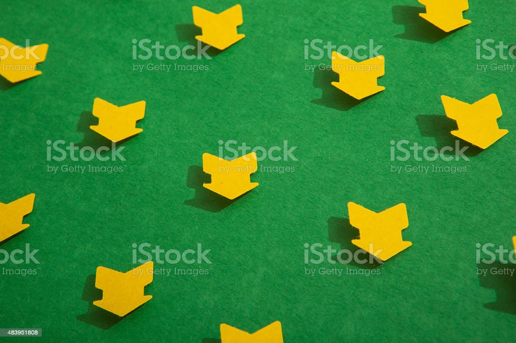 Cutout yellow arrows on a green background stock photo