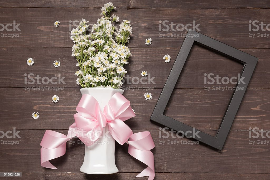 Cutter flowers and picture frame are in vase on wooden stock photo