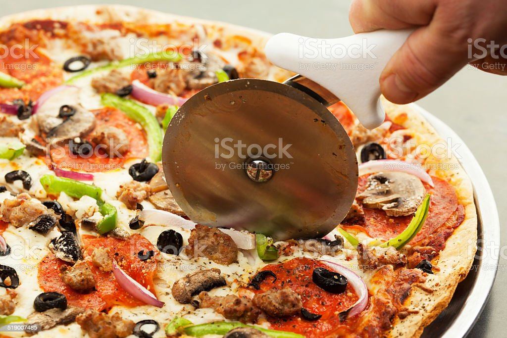 Cutter Slicing A Supreme Thin Crust Pizza stock photo