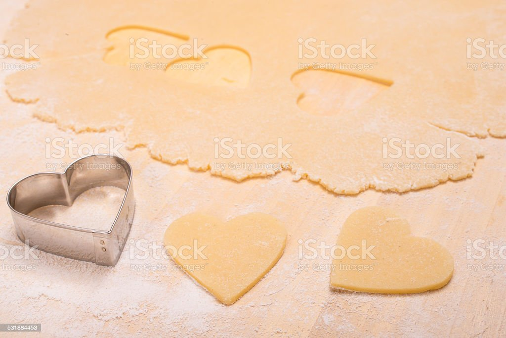 Cutter with heart shape of dough stock photo