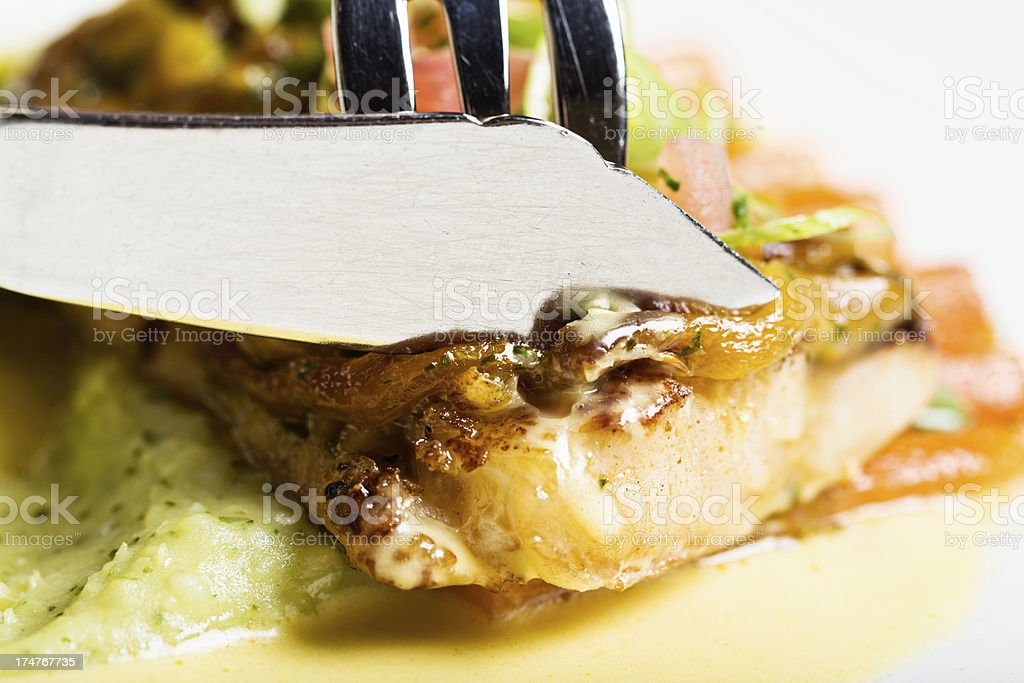 Cutting a slice from delicious-looking grilled fish dish stock photo