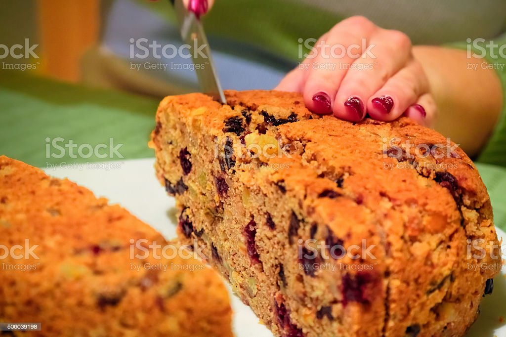 Cutting a slice of Panettone (Italian Christmas cake) stock photo