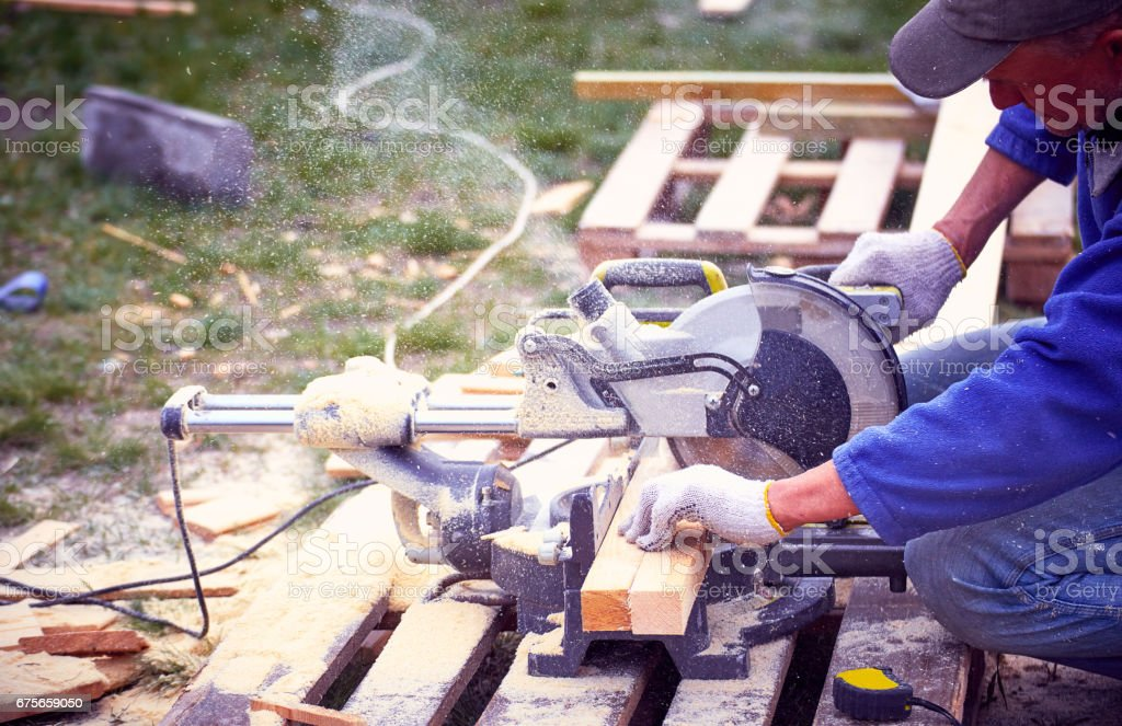 Cutting a tree with a circular saw in the workplace. stock photo
