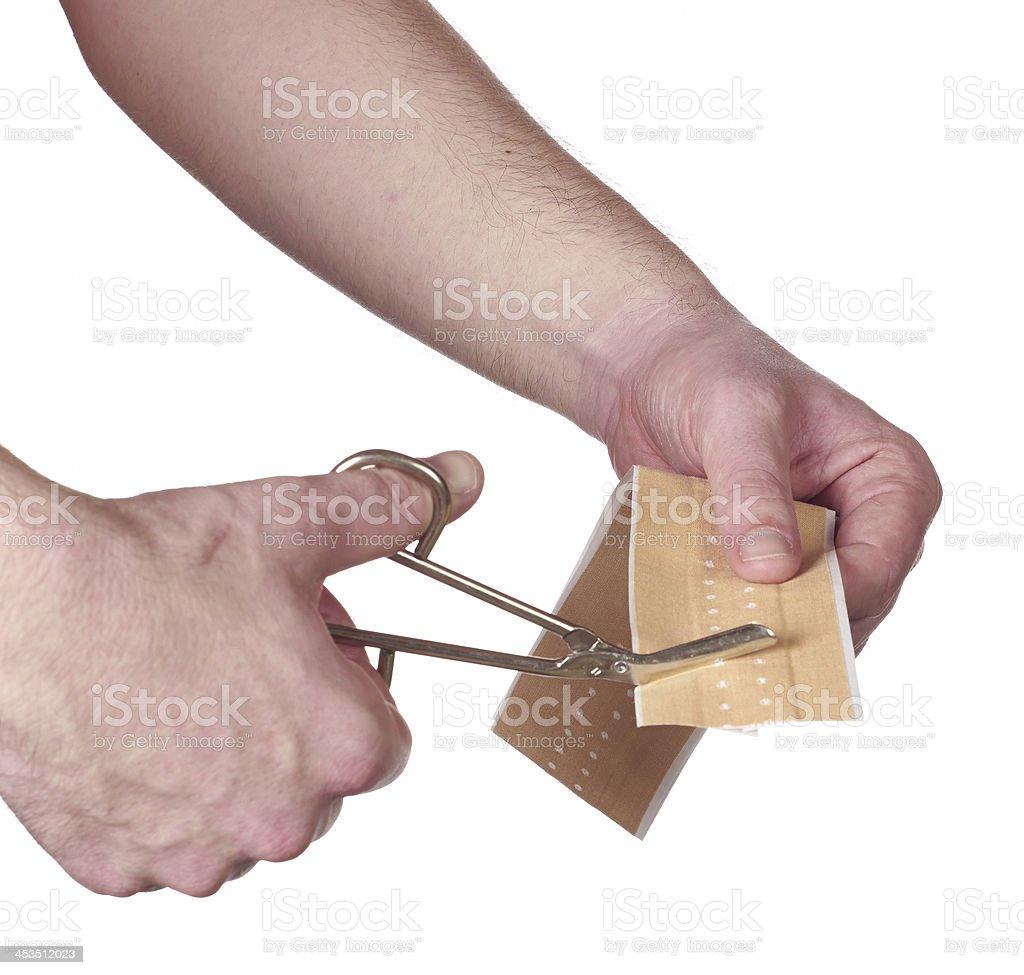 Cutting adhesive bandage stock photo