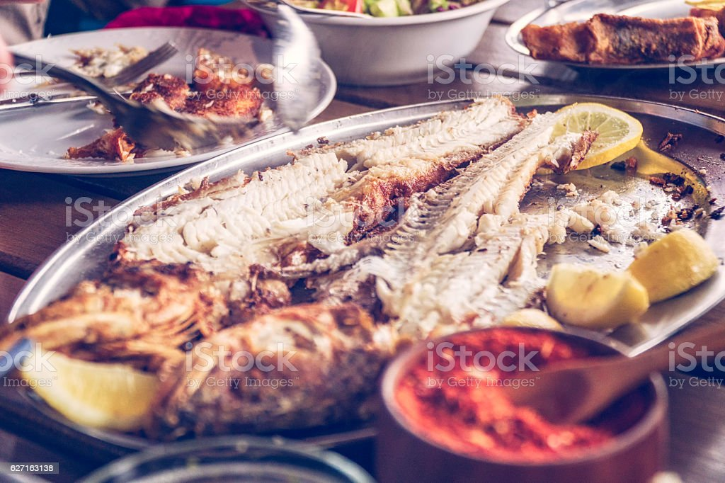 Cutting and Filleting Grilled Fish in a Restaurant stock photo