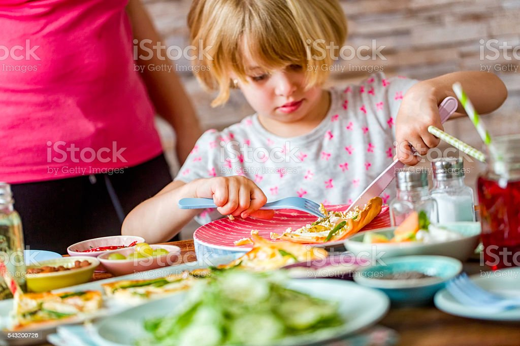 Cutting Asparagus Tart with Kitchen Knife stock photo