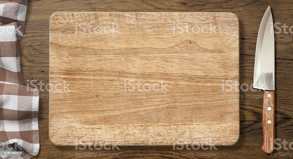 Cutting board and knife on old table with picnic tablecloth stock photo