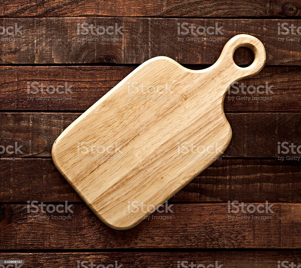 Empty cutting board on a dark wooden table. View from above