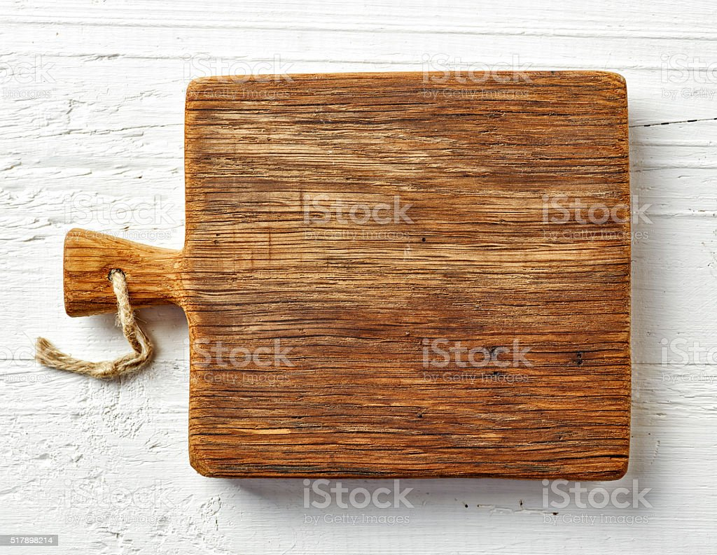 Cutting board on white wooden table stock photo