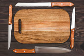 cutting board on wooden background with knifes