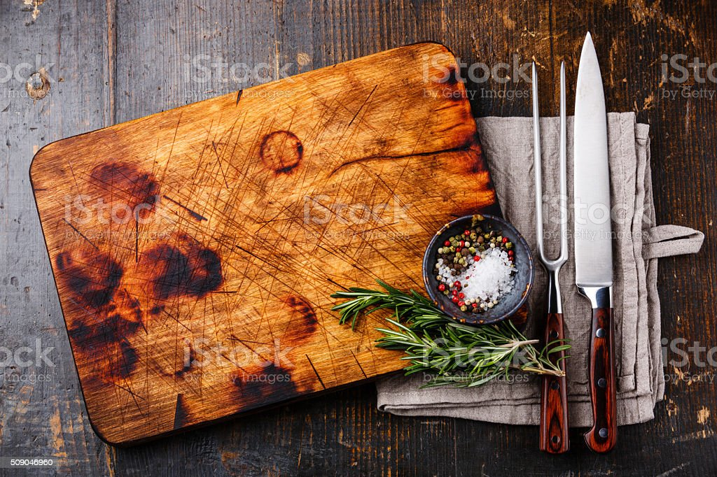 Cutting board, pepper and rosemary with fork and knife stock photo