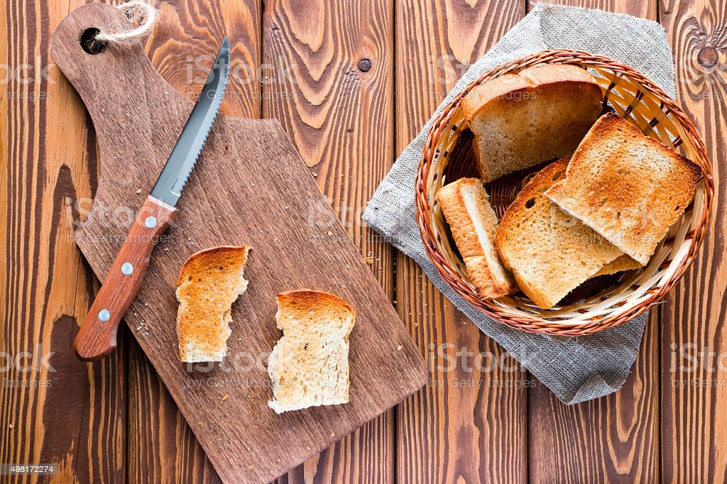 cutting board with a knife and a basket of toast stock photo