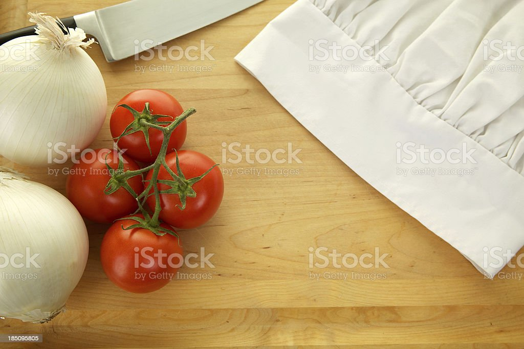 Cutting Board with Chef Hat Knife Tomatoes Onion Background stock photo