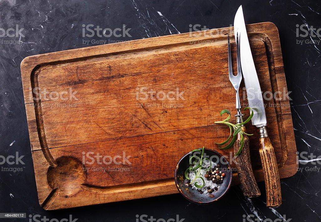 cutting board with fork and knife carving set stock photo