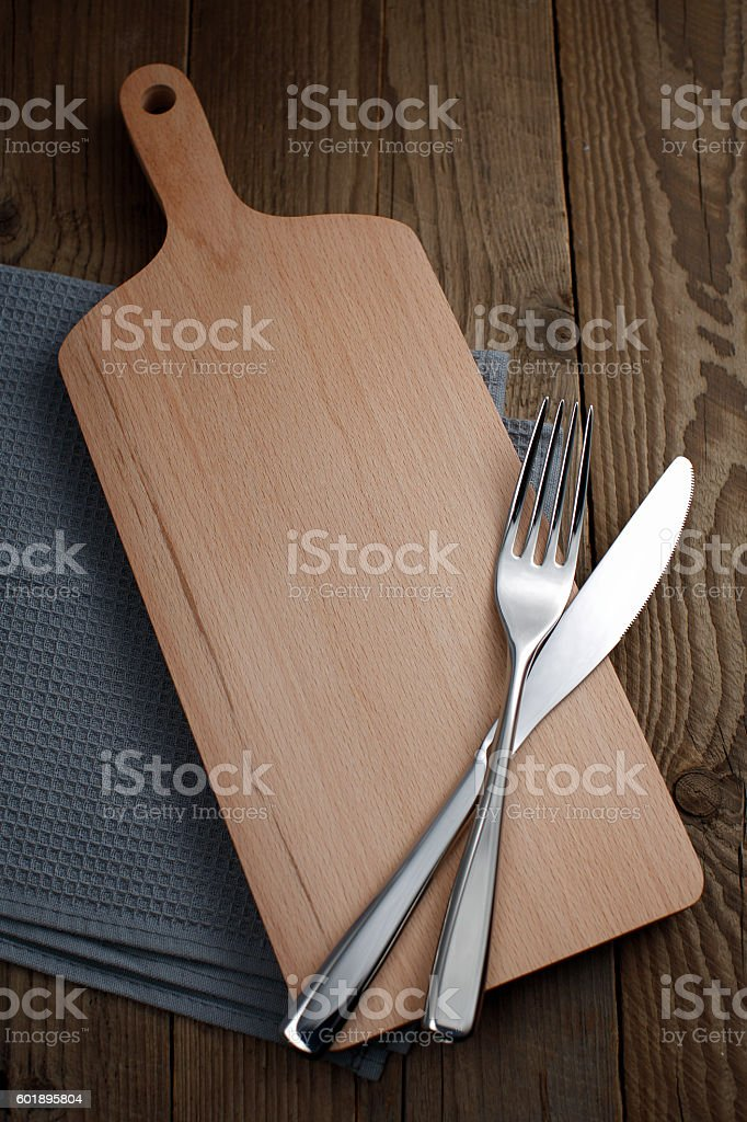 Cutting board with fork and knife stock photo