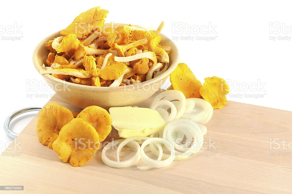 cutting board with golden chanterelle mushroom (Cantharellus cibarius) and onions stock photo