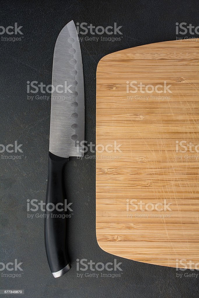 Cutting board with knife on black counter stock photo