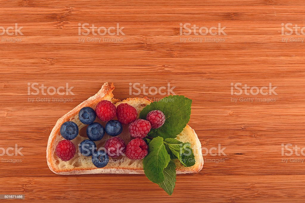 Cutting board with sandwich of blueberries and raspberries on br royalty-free stock photo