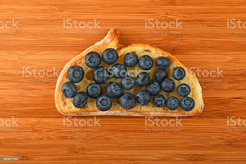 Cutting board with sandwich of blueberries on slice of bread royalty-free stock photo