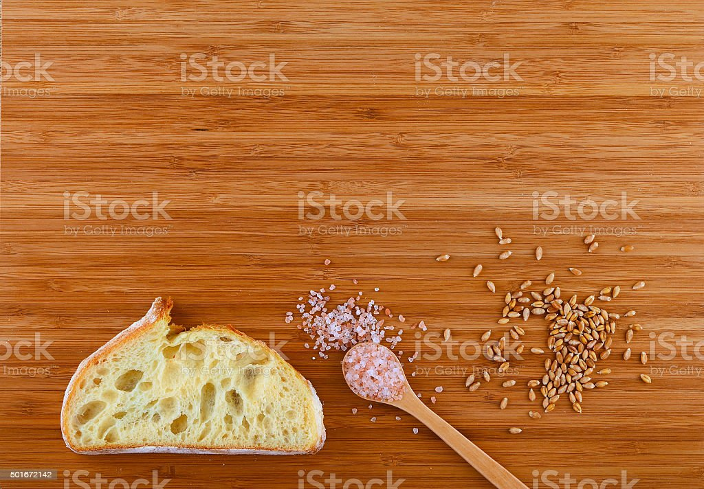 Cutting board with spoon of Himalayan  salt, wheat grains royalty-free stock photo