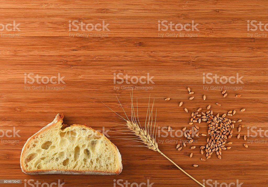 Cutting board with wheat ear, grains and slice of bread royalty-free stock photo